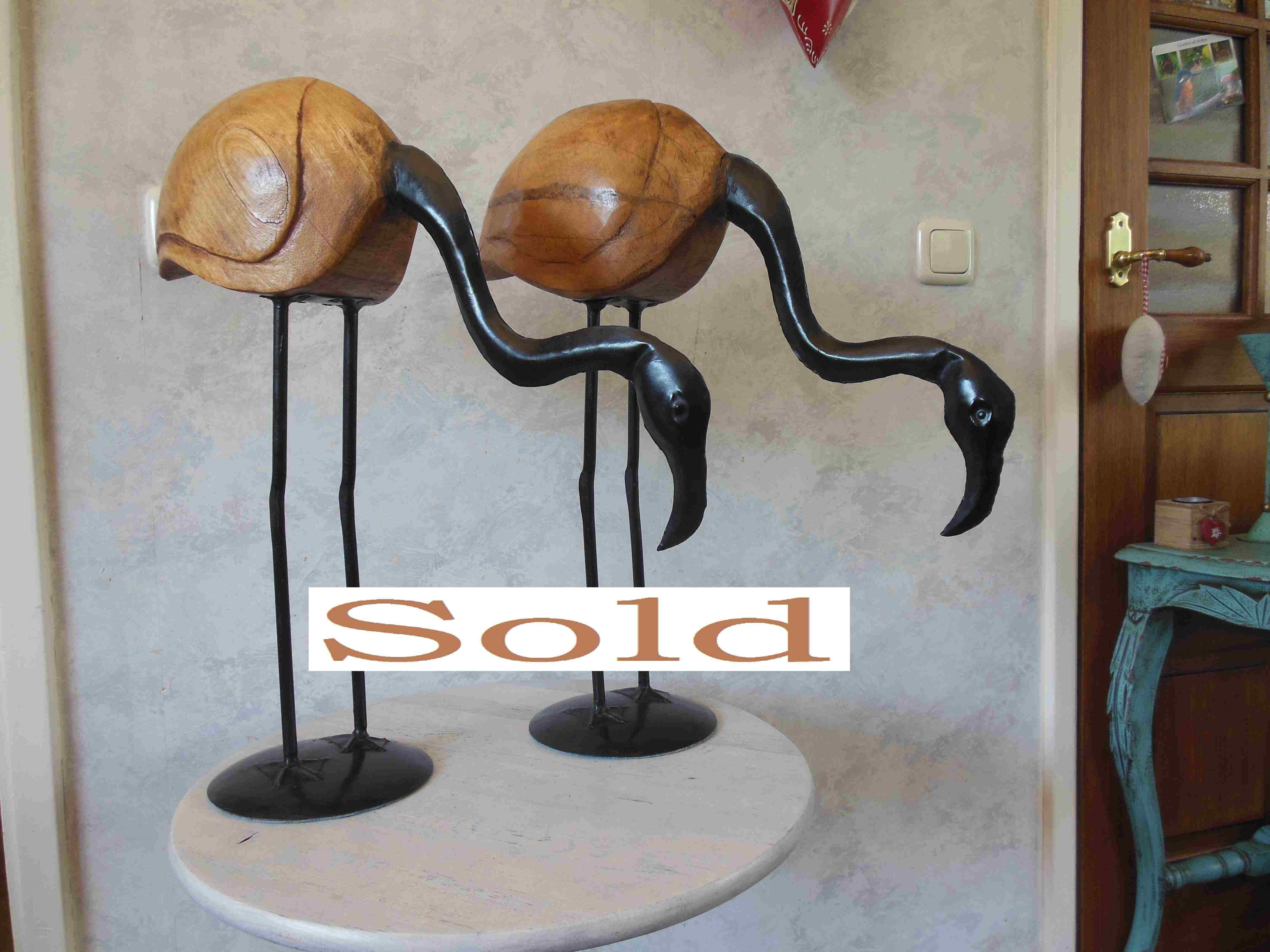 Two elegant flamingos made of wood and black metal with beautiful details.