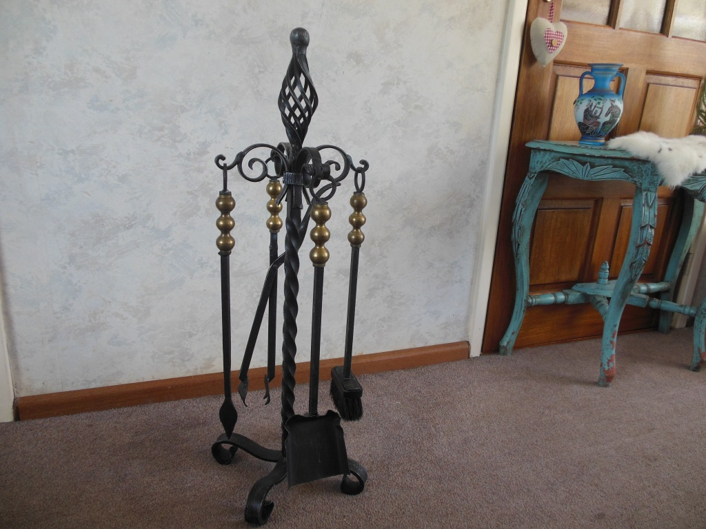 Beautiful heavy wrought iron fire irons with gold colored handles including a shovel, brush, tong and poker.