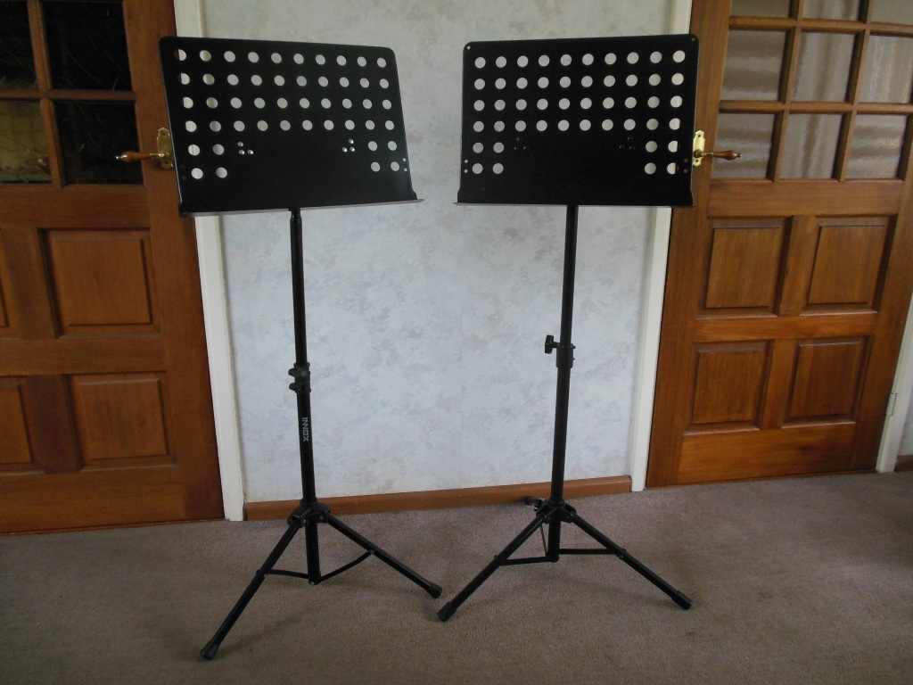 Two sturdy black music stands or menu boards or menu standards with perforated sheet e.g. for displaying restaurant menus.