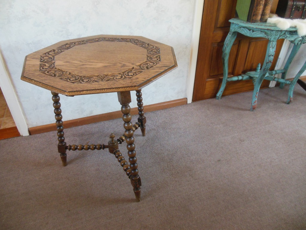 oak bobbin table with with octagonal table top decorated with a band of floral motifs.